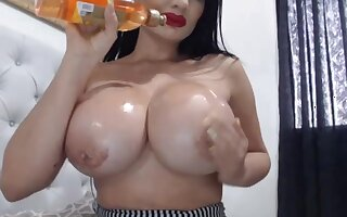 Buxom MILF oils up her huge boobs