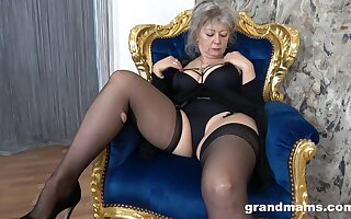 Dirty granny about baneful lingerie coupled with stockings moans while playing