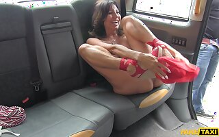 Busty mature Tara Holiday flashes her big juggs to the taxi driver