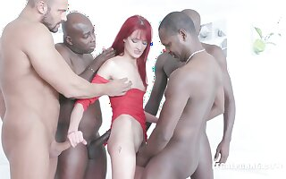 Red haired woman, Andi Rye is kneeling on the floor and sucking a big, black cock